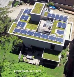 Aerial view of low rise residential home with solar photovoltaic panels and green roof.
