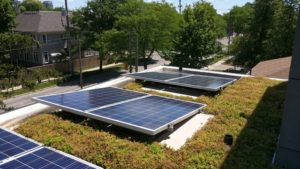 Two solar photovoltaic panels combined with green roof on a residential home in the city.